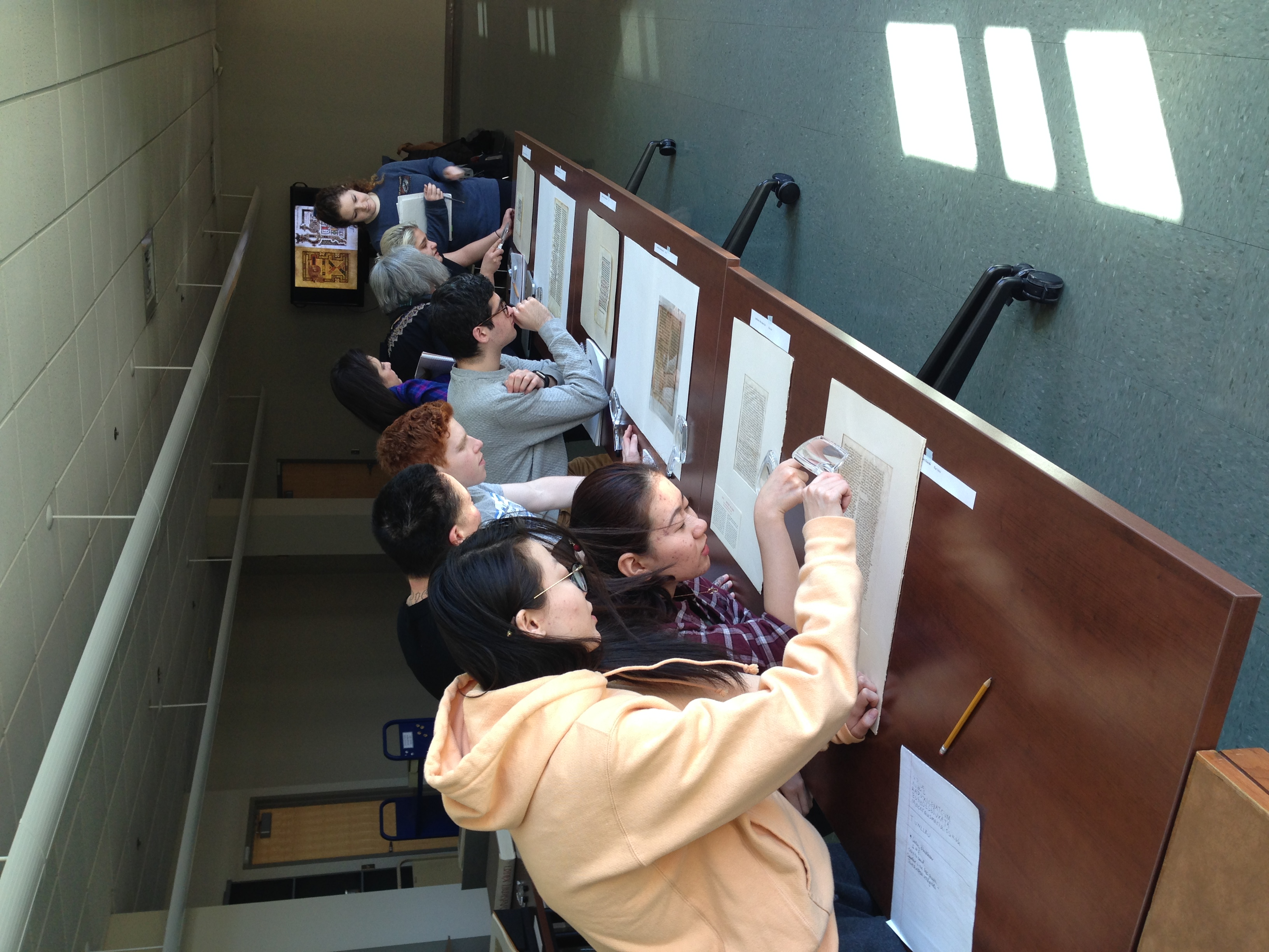 Students in a classroom studying premodern manuscripts